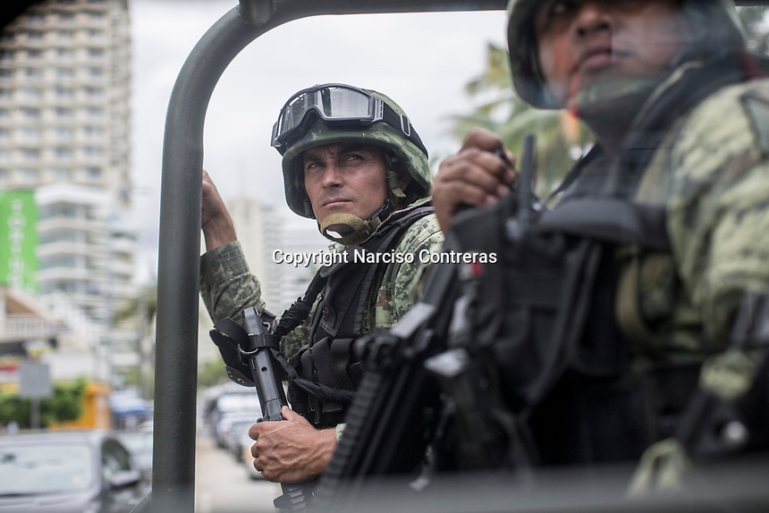 June 17, 2018: Mexican army soldiers surveil the touristic boulevard in downtown Acapulco, Guerrero. A juncture of security forces, among them military, marines, federal police and local police joined under one-command to fight crime violence in the once-glamorous resort destination.