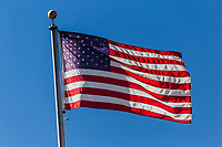 The U. S. Flag waves in the breeze on top of a flag pole and against a blue sky at an East Bay Regional Park in northern California