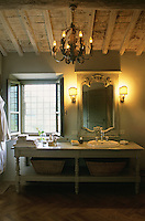 A converted French table houses the basin in this rustic bathroom