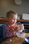 Berkeley, CA Girl, eighteen months old, inventing a new way to eat her food while lunching at home  MR