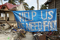 "Philippines. Province Eastern Samar. Hernani. 95 % of the town was destroyed by typhoon Haiyan's winds and storm surge. The population has writen on a banner: "" Help us. We need food."" Typhoon Haiyan, known as Typhoon Yolanda in the Philippines, was an exceptionally powerful tropical cyclone that devastated the Philippines. Haiyan is also the strongest storm recorded at landfall in terms of wind speed. Typhoon Haiyan's casualties and destructions occured during a powerful storm surge, an offshore rise of water associated with a low pressure weather system. Storm surges are caused primarily by high winds pushing on the ocean's surface. The wind causes the water to pile up higher than the ordinary sea level. 25.11.13 © 2013 Didier Ruef"