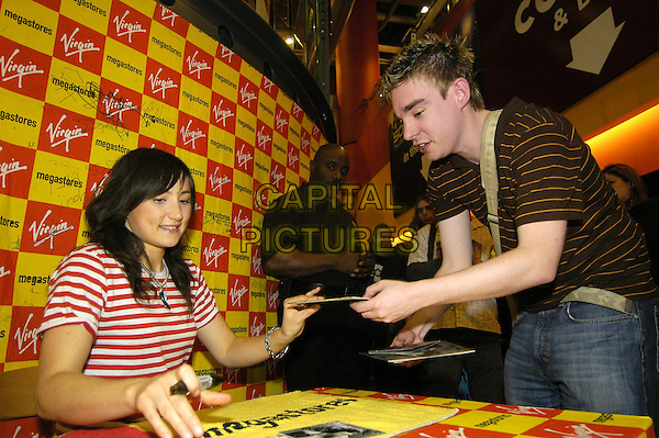 KT TUNSTALL.In Store Gig & Signing at Virgin Megastore, Oxford Street, London.May 10th, 2005.half length red and white striped shirt singing autographs fan.www.capitalpictures.com.sales@capitalpictures.com.©Capital Pictures