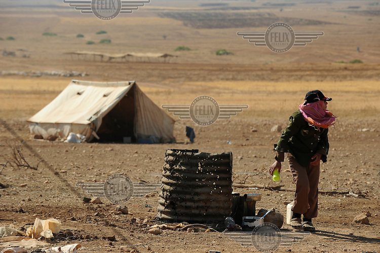 A relative of Ghayad Abed El Mahdi Salamin, next to a makeshift oven at the family's encampment encampment in Hadidyeh in the Jordan Valley. The Bedouin living here have been issued with eviction orders by Israeli authorities......