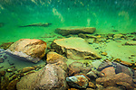 Close up of Lower Reed Lake. Emerald green colors of water and reddish boulders. Hatcher Pass, Mat-Su Valley, Southcentral Alaska, Summer.