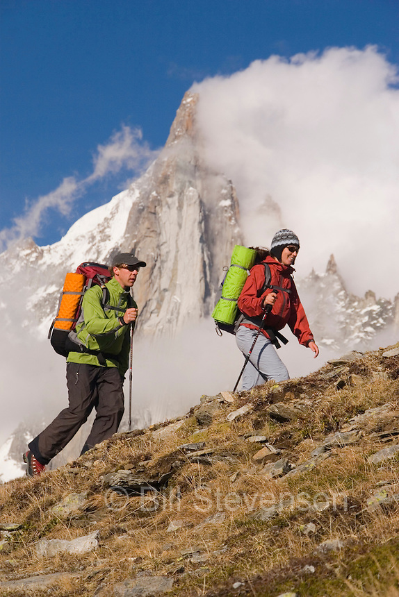 Two hikers climbing up a ridge