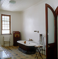 An old-fashioned style bathroom is furnished with an antique free-standing bath