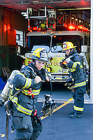 Nick Gosik (left) and J.T Boyle put on their gear at Eddington Fire Company Wednesday August 5, 2015 in Bensalem, Pennsylvania. (Photo by William Thomas Cain)