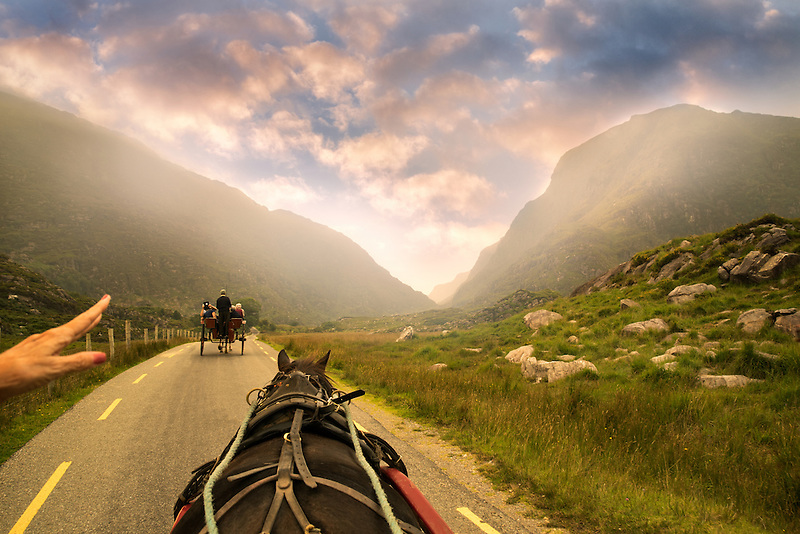 Horse drawn Jaunting Car on road with hand pointing the way. Gap of Dunloe, Ireland