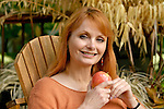 Mature woman holding apple, smiling, portrait