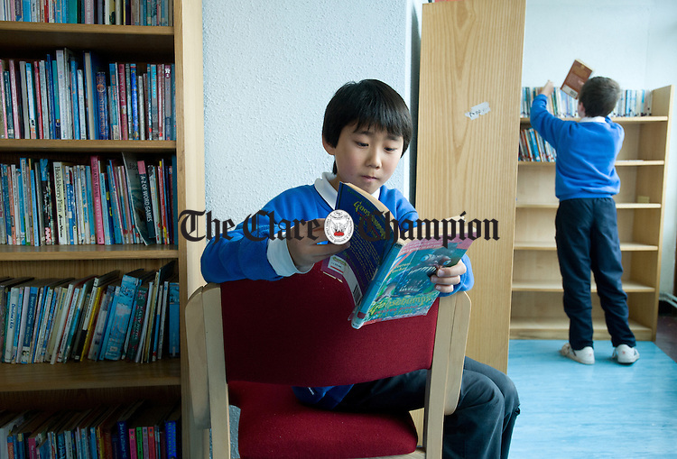William Zhou reading a book in the library at the Holy Family Senior school in Ennis. Photograph by John Kelly.