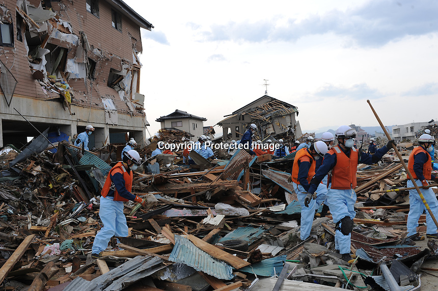 A search and rescue team look through the remains of a houses in the town of Natori, after the Tsunami devastated the entire pacifc coastline of Japan after the earthquake and tsunami devastated the area Sendai, Japan.<br />