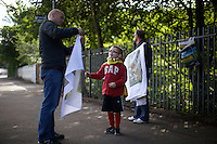 Around 70,000 people celebrate open-air mass at Bellahouston park, Glasgow for the visiting Pope Benedicte XVI on the first state visit to Scotland...A boy has his flag mended by vendors outside the park.