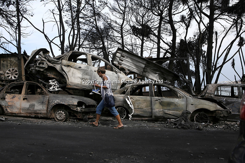 Pictured: A woman walks next to piles of destroyed cars in the aftermath of the forest fire which has claimed dozens of lives in the Mati area of Rafina, Greece. Tuesday 24 July 2018<br /> Re: Deaths caused by wild forest fires throughout Greece.