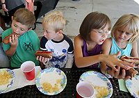 NWA Democrat-Gazette/DAVID GOTTSCHALK   Liam Campbell (from left), 7, Wesley Crum, 6, Dezi White, 8, and her sister Rae White, 6, eat Tuesday, July 11, 2017, turkey dogs on wheat buns in the Healthy Cooking Class while at the Zing! Day Camp summer youth program at the Donald W. Reynolds Boys and Girls Club in Fayetteville. Campers in Zing! rotate through activities that include swimming, gymnastics, the healthy cooking classes and legos. The program is offered Monday through Friday in the morning and the themes change weekly.