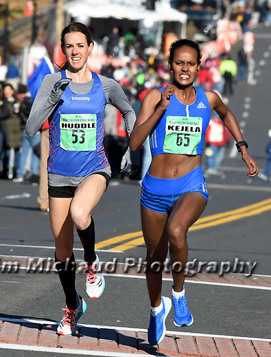 The female runners in a near photo finish, Molly Huddle and 65, Buze Diriba Kejela, at the finish line, during the 81st running of the Manchester Road Race, Thursday, November 23, 2017, in  Manchester. (Jim Michaud / Journal Inquirer)