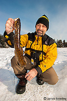 Ice fisherman holding a ling fish.