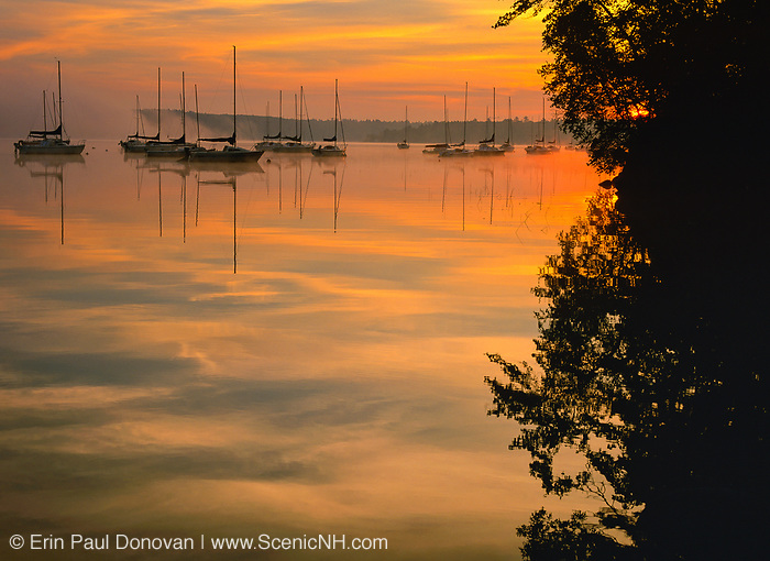 Reflection of sailboats in Lake Massabesic in Auburn, New Hampshire USA at sunrise.