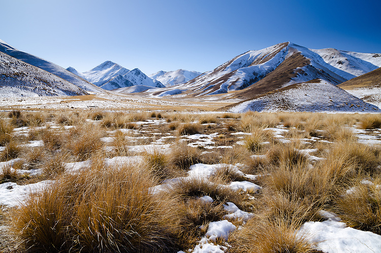 Snow covered hills and tussock grasses on a sunny winter day. Lindis Pass, Central Otago, South Island, New Zealand - stock photo, canvas, fine art print