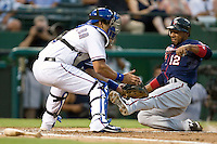 Minnesota Twins second baseman Alexi Casilla #12 slides home safely in front of catcher Yorvit Torrealba #8 during a Major League Baseball game against the Texas Rangers at the Rangers Ballpark in Arlington, Texas on July 27, 2011. Minnesota defeated Texas 7-2.  (Andrew Woolley/Four Seam Images)