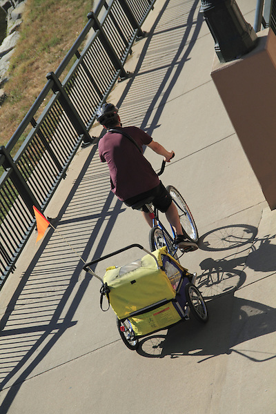 Father riding bike and pulling a baby carriage on a sidewalk in Denver, Colorado. .  John offers private photo tours in Denver, Boulder and throughout Colorado. Year-round.