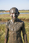 Model released image of young boy covered in mud from playing in muddy pool, Butley Creek, Suffolk, England