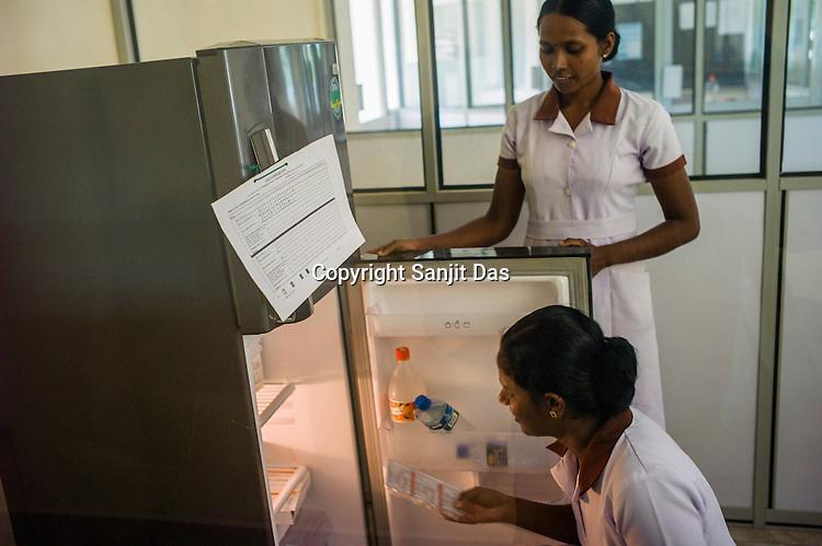 Mathumita pulls out vaccines from the fridge at the government health centre in Tharmapuram in North Kilinochchi, Sri Lanka.  Photo: Sanjit Das/Panos