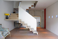 Spacious hallway with cantilevered style staircase and wooden floor