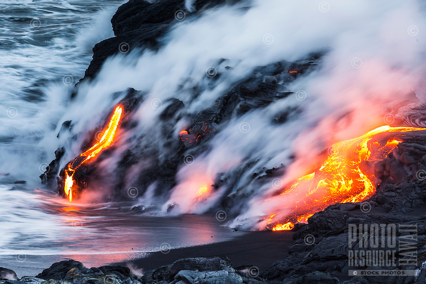 While sunset turns to dusk, steam rises as glowing lava meets the Pacific Ocean, Big Island of Hawai'i.