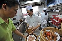 The kitchen of Mak Pui Gor,50, (green shirt)  in Tim Ho Wan the cheapest Michelin starred restaurant in the world, Hong Kong..17-Jul-11..Photo by Richard Jones......