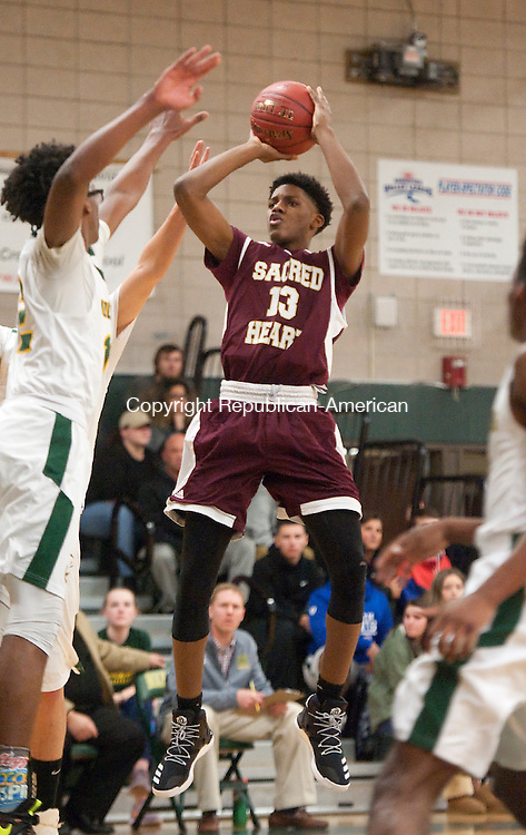 WATERBURY,  CT-010317JS13-- Sacred Heart's Omar Rowe (13) puts up a shot over Holy Cross' Marcellus Gomes (12) during their game Tuesday at Holy Cross High School in Waterbury. Jim Shannon Republican-American