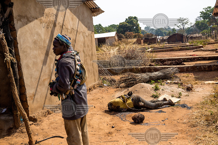 The head and decapitated body of a man lie on the ground beside an Anti-Balaka fighter. The dead man was accused of robbing an elderly villager. In 2013 a rebellion by a predominantly Muslim rebel group Seleka, led by Michel Djotodia, toppled the government of President Francios Bozize. Djotodia declared that Seleka would be disbanded but as law and order collapsed the ex-Seleka fighters roamed the country committing atrocities against the civilian population. In response a vigillante group, calling themselves Anti-Balaka (Anti-Machete), sought to defend their lives and property but they then began to take reprisals against the Muslim population and the conflict became increasingly sectarian. French and Chadian peacekeeping forces have struggled to contain the situation and the smaller Muslim population began to flee the country.