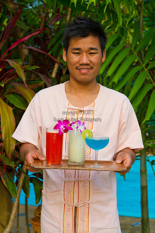 Elephant Hills Luxury Tented Camp in the rainforest in Southern Thailand.  A waiter holding a tray of colorful cocktails.