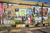 Young Couple walking along colorful art mural on East 6th Street in East Austin, Texas.