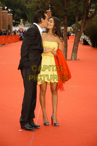 "JONATHAN RHYS MEYERS & REENA HAMMER.Premiere for film  ""August Rush"" during the .Rome International Film Festival, Rome, Italy, .October 20th 2007..full length couple  yellow strapless dress  suit white shirt purple shoes kissing.CAP/CAV.©Luca Cavallari/Capital Pictures."