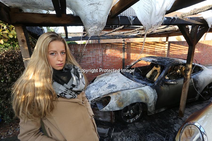 BNPS.co.uk (01202 558833)<br /> Pic: RichardCrease/BNPS<br /> <br /> ***Please use full byline***<br /> <br /> Eloise Towning with her parents' destroyed cars.<br /> <br /> Crime novelist Andrew Towning fears life is imitating art after an arsonist torched his Porsche car in a copycat attack of one of his storylines.<br /> <br /> The best-selling author believes the offender was inspired to set fire to his &pound;18,000 Porsche Carrera after reading one of his Jake Dillon crime-thriller novels.<br /> <br /> The blaze caused a small explosion and sent flames 10ft into the air.<br /> <br /> In his 2010 book 'Shroud of Concealment', the lead character has his own Porsche 911 car blown up in the street after being targeted by a underworld crime gang.<br /> <br /> Now Mr Towning fears he has been singled out by one of his readers following the attack at his home in Merley, near Wimborne, Dorset.