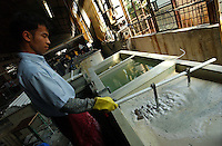 Worker dips the metal into acid for cleaning at a factory in Zhouqing, Guangdong Province, China. The factory makes promotional gift items..06 May 2005