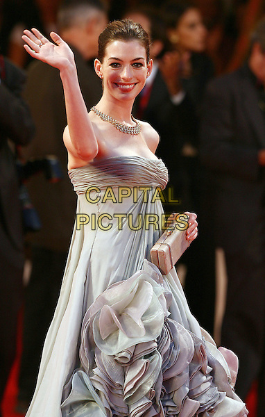 "ANNE HATHAWAY.""Rachel Getting Married' premiere during the 65th Venice Film Festival, Venice, Italy..September 3rd, 2008.half length grey gray strapless dress white beige ruffled ruffles gown blue purple clutch bag necklace hand arm waving .CAP/ADM/Liverani.©Liverani/AdMedia/Capital Pictures"