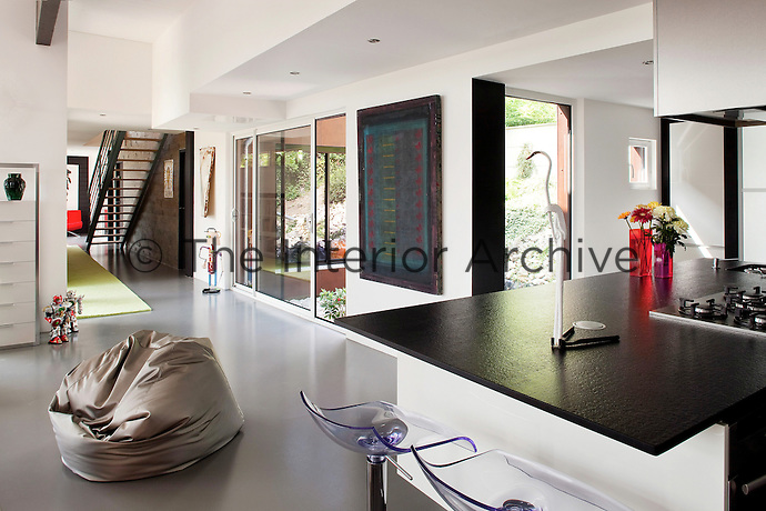 An open plan ground floor living area is dominated at one end by a contemporary kitchen island with a black granite worktop