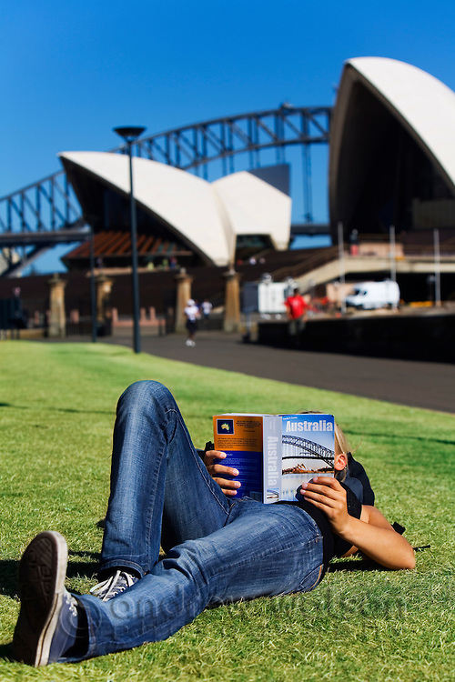 A woman reads her guidebook on the lawn in front of the Sydney Opera House.  Sydney, New South Wales, AUSTRALIA.