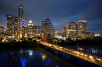 This panoramic Austin skyline image features downtown Austin as Bat Watchers gather on the Congress Avenue Bridge during the annual Bat Fest to watch 1.5 million Mexican free-tailed bats emerging from under the bridge at dusk, 3 stages with live music, more than 75 arts & crafts vendors, delicious food and drinks, fun children's activities, a bat costume contest and other bat activities, over Lady Bird Lake in downtown Austin, Texas - Stock Image.