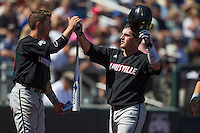 Louisville catcher Kyle Gibson (14) is greeted by teammate Sutton Whiting (17) against the Oregon State Beavers during Game 5 of the 2013 Men's College World Series on June 17, 2013 at TD Ameritrade Park in Omaha, Nebraska. The Beavers defeated Cardinals 11-4, eliminating Louisville from the tournament. (Andrew Woolley/Four Seam Images)