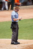 Home plate umpire R.J. Dyett inspects a baseball during the Carolina League game between the Frederick Keys and the Winston-Salem Dash at BB&T Ballpark on July 30, 2014 in Winston-Salem, North Carolina.  The Dash defeated the Keys 12-2.   (Brian Westerholt/Four Seam Images)
