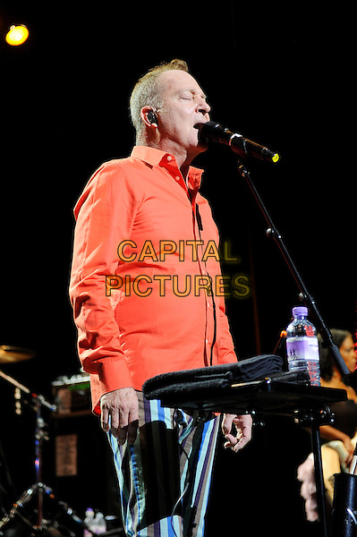 Fred Schneider<br /> The B 52's performing in concert, Indigo2, Greenwich, London, England. 16th August 2013<br /> on stage in concert live gig performance performing music half length orange shirt blue white stripe trousers singing side profile    <br /> CAP/MAR<br /> &copy; Martin Harris/Capital Pictures