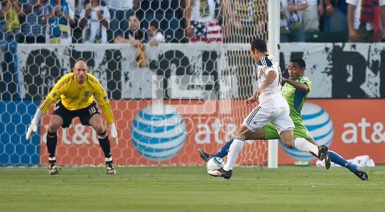 LA Galaxy midfielder Landon Donovan (10) and Seattle Sounders defender James Riley (7) battle for the ball as Sounders goalie Kasey Keller (18) watches during the first half of the game between LA Galaxy and the Seattle Sounders at the Home Depot Center in Carson, CA, on July 4, 2010. LA Galaxy 3, Seattle Sounders 1.