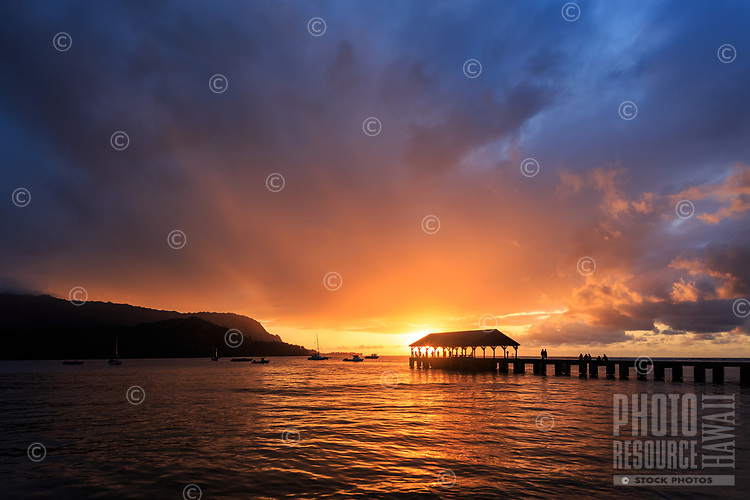 A brilliant sunset bursts through the clouds and reflects on the waters of Kaua'i's Hanalei Bay, with Hanalei Pier in silhouette.