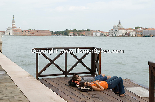 Venice Italy 2009. Tourist couple asleep , The church of San Giorgio Maggiore ( left ) The churh of  on La Giudecca. Canale della Giudecca.