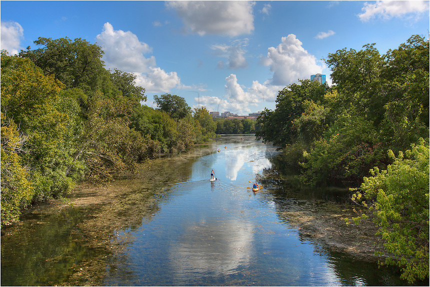Canoers and Paddle Boarders enjoy a warm September morning on the waters of Lady Bird Lake in Zilker Park, one of Austin, Texas' favorite outdoor areas.
