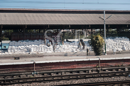 Amritsar, Punjab, India. Rice bags stacked on a platform at the station waiting to be loaded onto trains with workers ready and a truck delivering more.