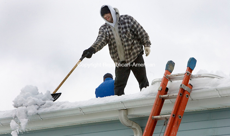 WOLCOTT, CT. 08 February 2011-020811SV11--Marco Santos of Rays Remodeling and Construction shovels the top of the American Legion Post 165 in Wolcott Tuesday. The American Legion had some leaking and was trying to avoid a roof collapse.<br /> Steven Valenti Republican-American