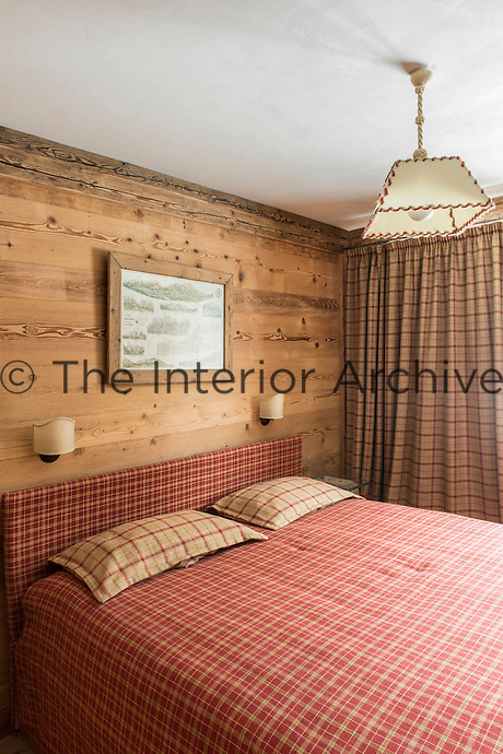 A bedroom in a traditional style wood panelled chalet with red checked bedding and matching headboard